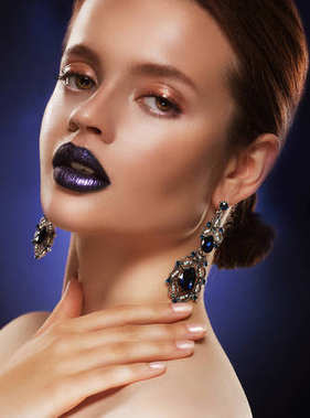 Fashion portrait of young beautiful woman with jewelry. Perfect make-up. Blue lips.
