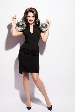 Beautiful young sensual woman wearing black dress and holding disco ball