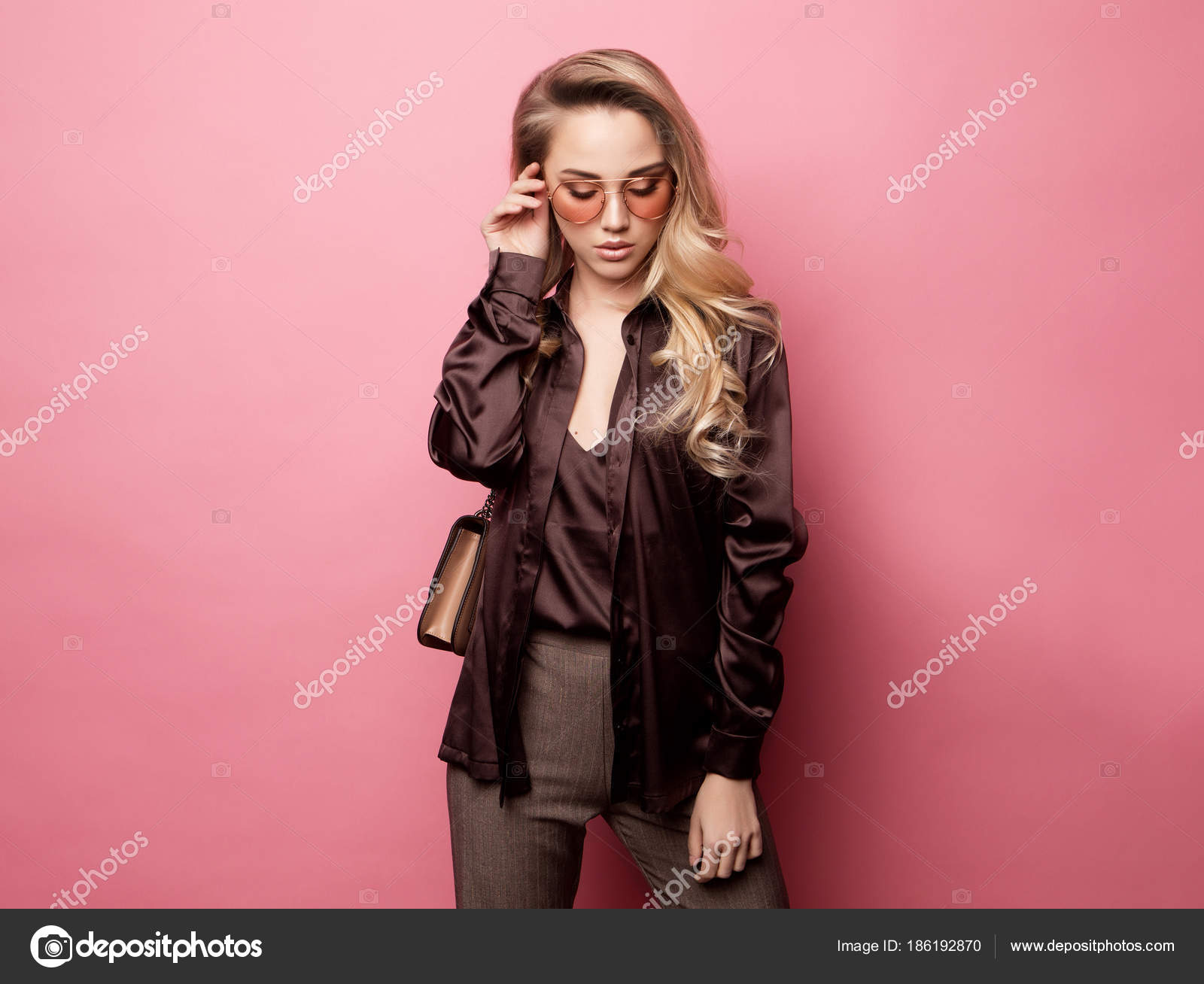 e9878c13f7402 Beautiful blond woman in a blouse and pants wearing glasses