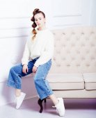 stylish teen girl in casual clothes sitting on sofa and posing