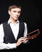 Young male make up artist holding shadow palette and brush.