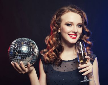 young woman holding a glass of wine and disco ball at night club