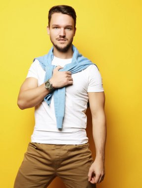 young man in smart casual wear looking at camera over yellow bac
