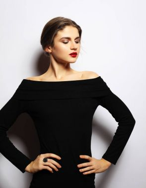 Young beautiful woman wearing black dress posing over white background