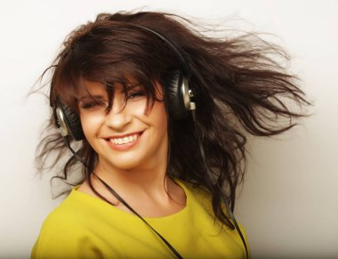 Woman with headphones listening music. Music girl dancing against white background.