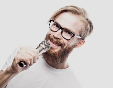 Boy Rocking Out. Image of a handsome bearded  man singing to the microphone. Emotional portrait of an attractive guy with a beard on a white background