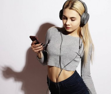 lifestyle and people concept: Beautiful young woman listening to music in headphones