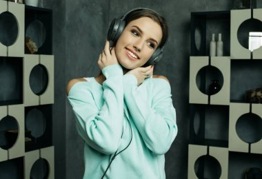 Young beautiful woman in casual outfit enjoying the music at home