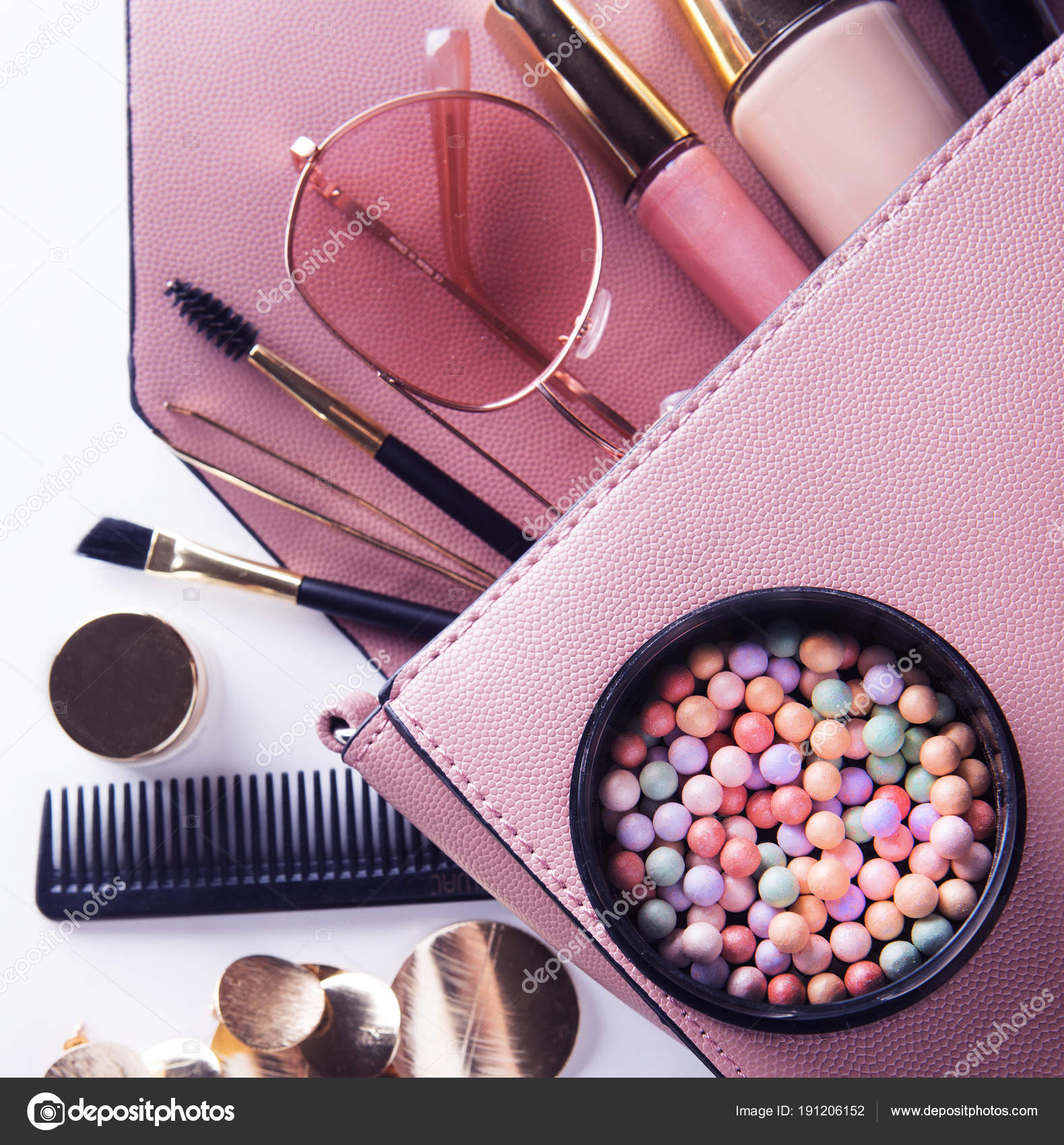 Makeup products with cosmetic bag on white background