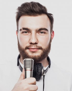 lifestyle and people concept: young man singing with microphone