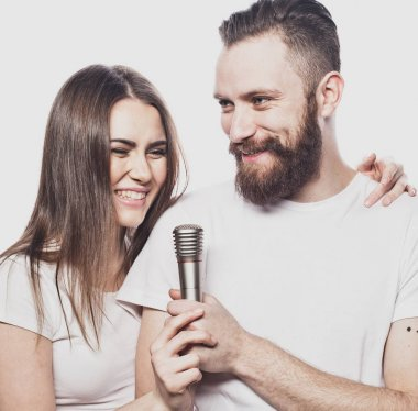 Happy couple singing in karaoke over white background,