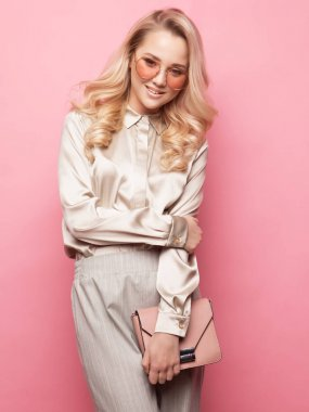 Beautiful blond woman in a blouse and pants wearing glasses, holding handbag