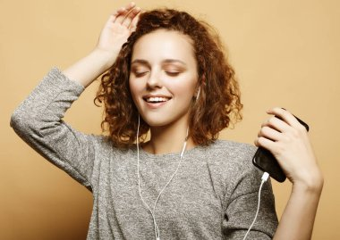 lifestyle and people concept: young woman in headphones listening to music smiling with closed eyes