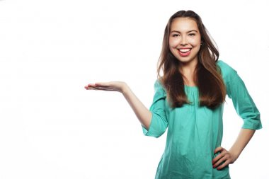 Young smiling woman points a hand with positive facial expressio