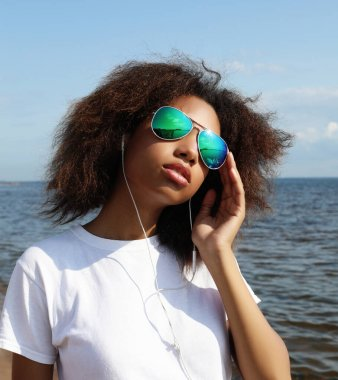 Charming amazing afro american young woman in sunglasses listening to music in headphones on her mobile phone. Dressed casual. Fun time outdoors near sea.