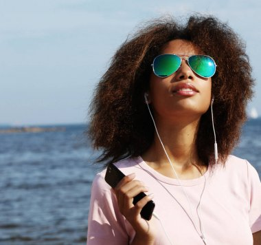 Charming amazing afro american young woman in sunglasses listening to music in headphones on her mobile phone. Dressed casual.
