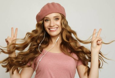lifestyle, emotion and people concept: Beautiful girl with long wavy hair listening to music