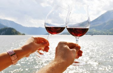 Wineglasses in hands against lake
