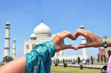 Heart-shaped hands against Taj Mahal.