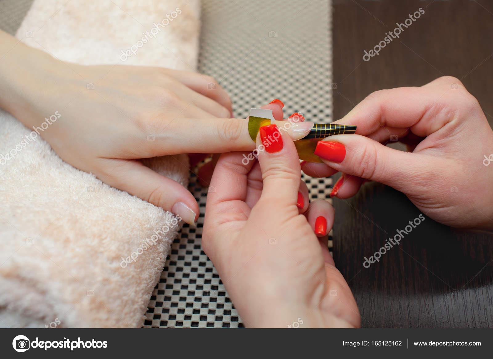 Der Meister der Nagellack setzt ein Fixiermittel am Finger vor die ...
