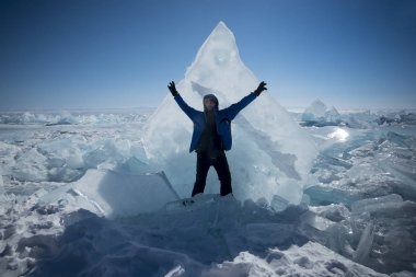 a tourist stands on the background of an ice block during the day against the blue sky in winter