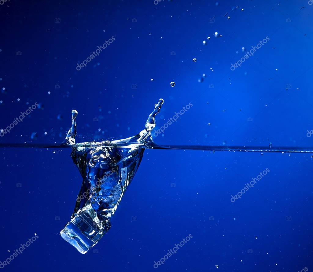 ice cube falling into water, close-up