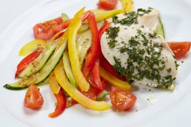 chicken with vegetables on white plate, close-up