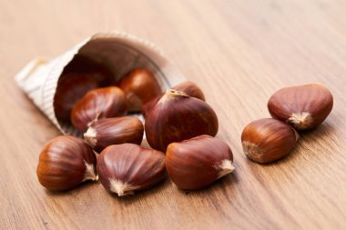 brown edible chestnut on wooden table, close-up