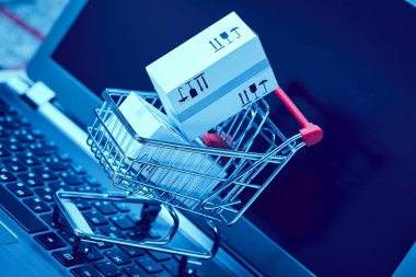 delivery packaging boxes in shopping cart on laptop keyboard