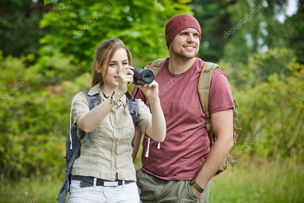 Two travelers with camera walking in forest at sunny day stock vector