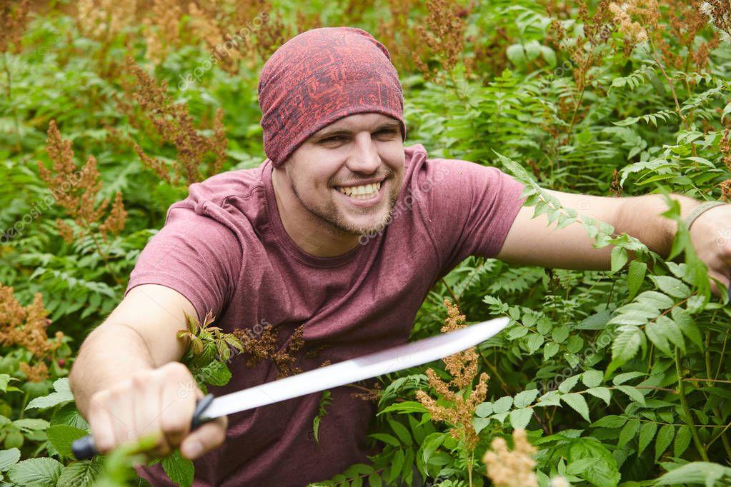 man with machete making way through thicket