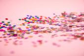 hromada barevných konfeti na růžovém pozadí