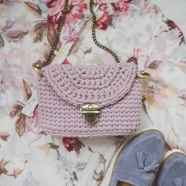 Flat lay of female fashion accessories and rose handbag on flower color background