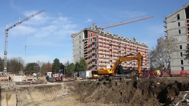 bagr a dělníci na staveništi