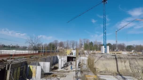 construction site with workers cranes and excavator