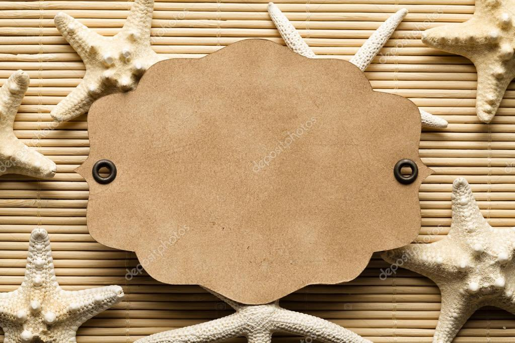 Starfishes and paper card on wooden background or texture