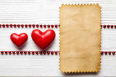 Fotografie Valentines Day - Two red hearts and blank paper card on white pl