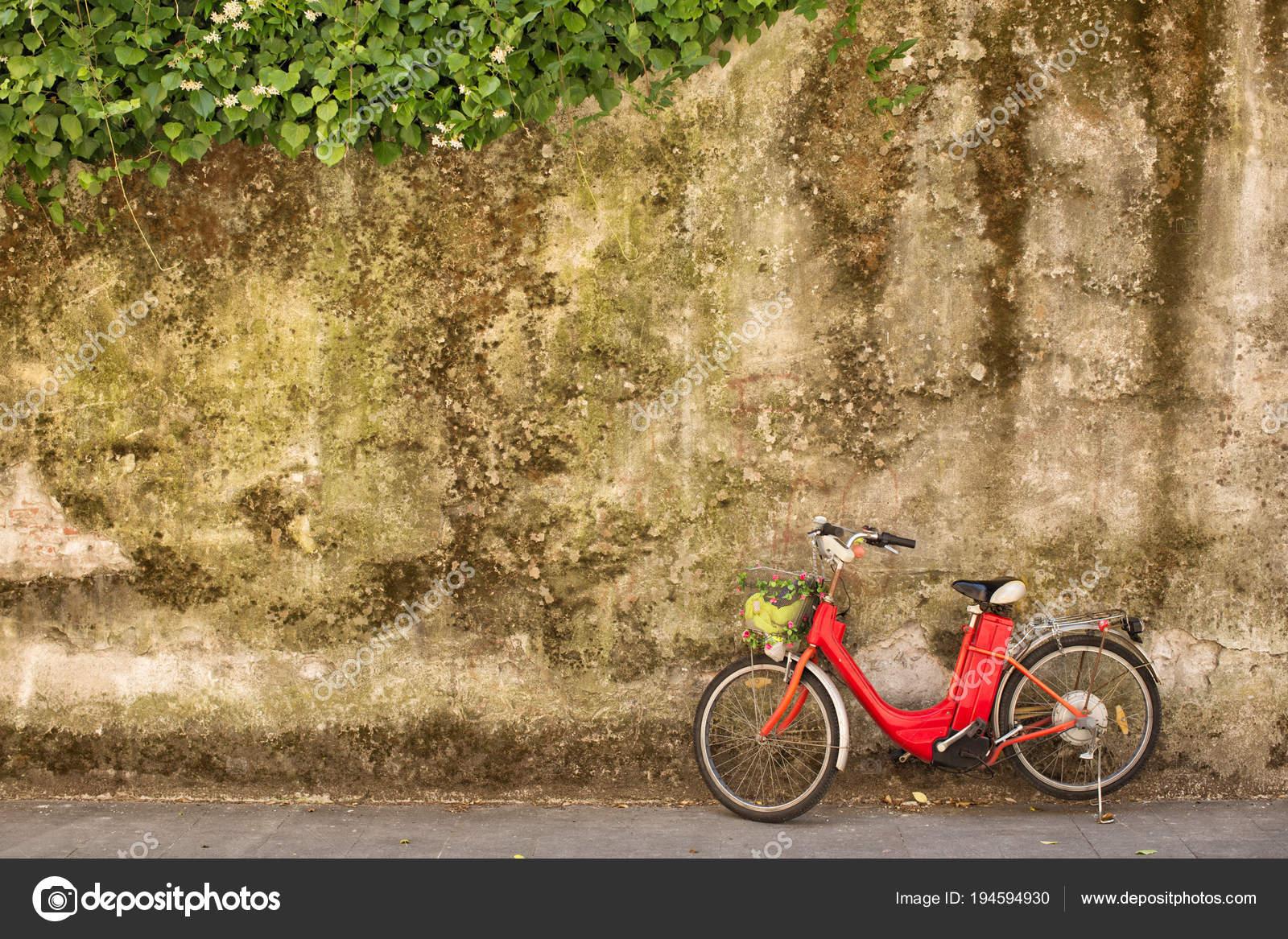 Bicicletta Elettrica Rossa Davanti Al Muro Di Pietra Foto Stock