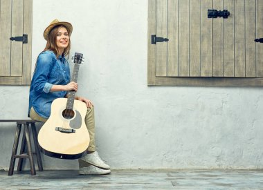 Smiling woman with guitar sitting on street bench