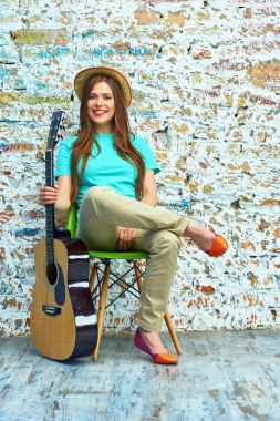 Smiling young woman sitting with guitar