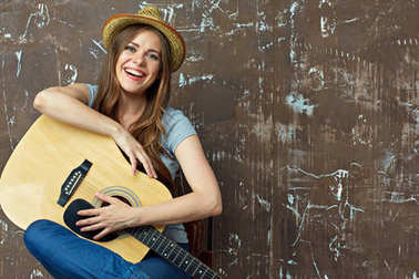 Young woman sitting with guitar on grunge wall background.