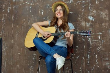 Smiling young woman portrait with acoustic guitar.
