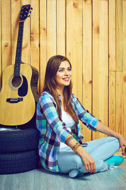 Woman sitting on floor with guitar and tires