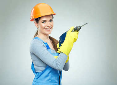 Woman builder holding drill tool