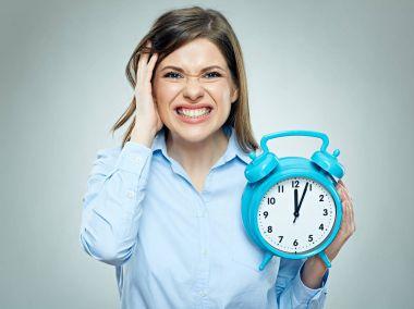 Scared businesswoman holding alarm clock