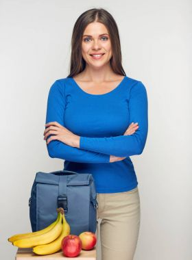 young woman with crossed arms standing near lunch bag and fruits