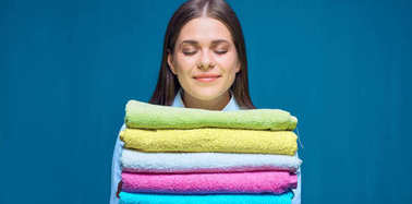 smiling woman with closed eyes holding pile of colorful towels on blue studio background