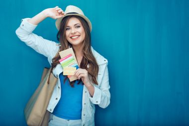 smiling woman holding passport and credit card, ready for travel concept