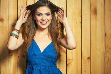 Beautiful woman with long hair in blue dress posing against yellow wooden wall