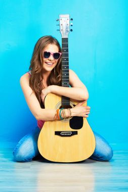 fashion music look with young model in sunglasses holding acoustic guitar and sitting on blue floor